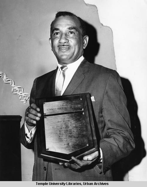 Cecil B. Moore holding an award