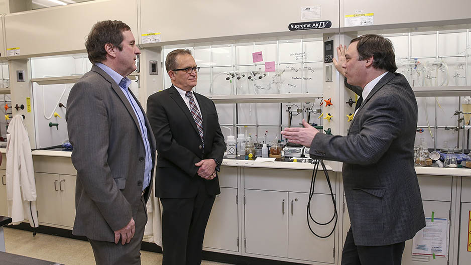 The CEO of Praeventix talks with Temple scientists in the lab.