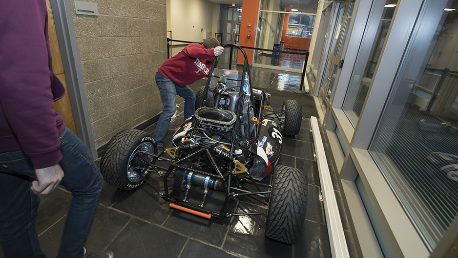 A student pushing the race car through a hallway.