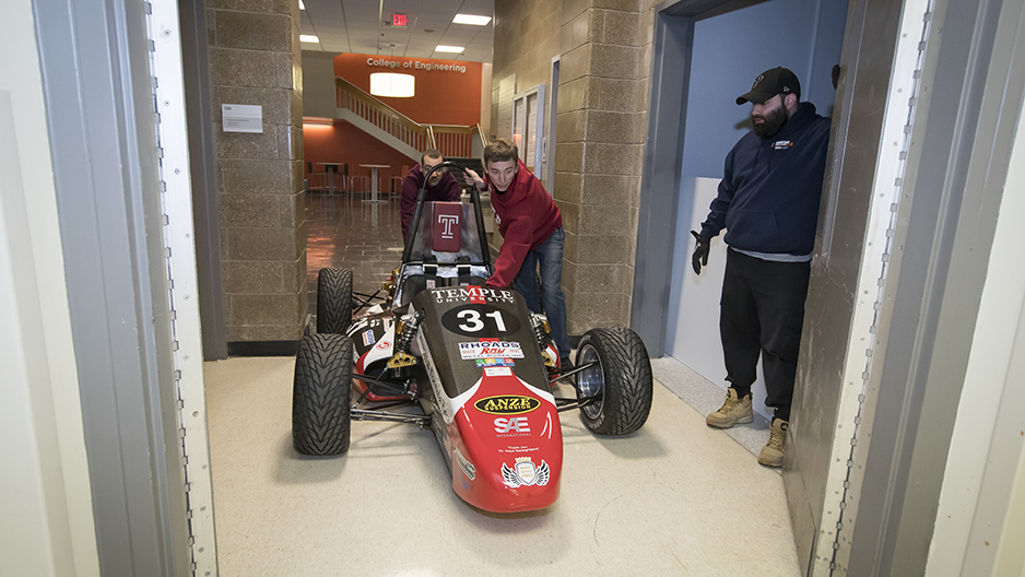 Two students pushing the race car past an elevator door.