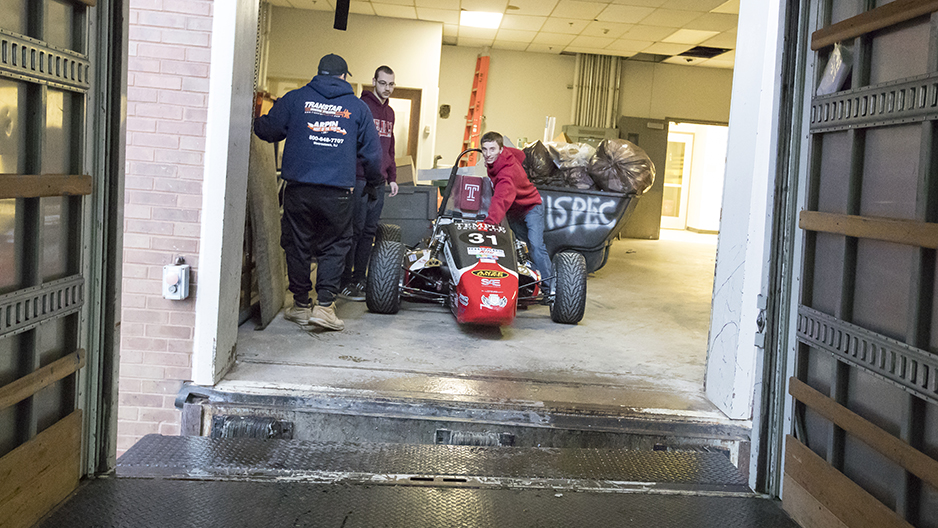 Two students pushing the race car towards a loading dock.