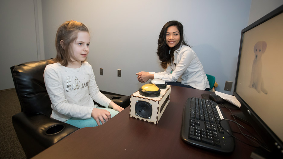 graduate student Zoe Ngo working with a child at a computer.