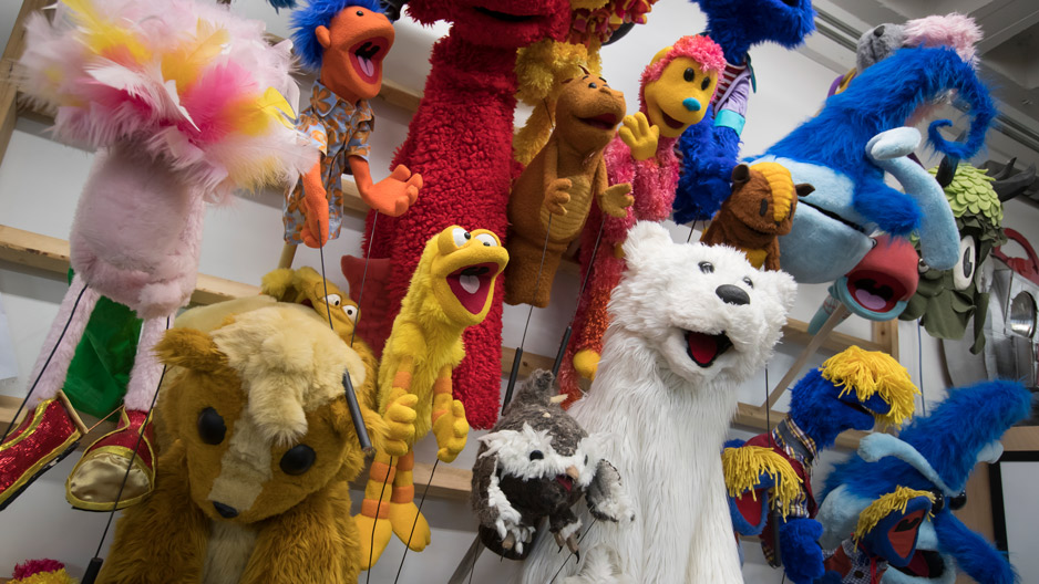 puppets hanging on the wall in a studio