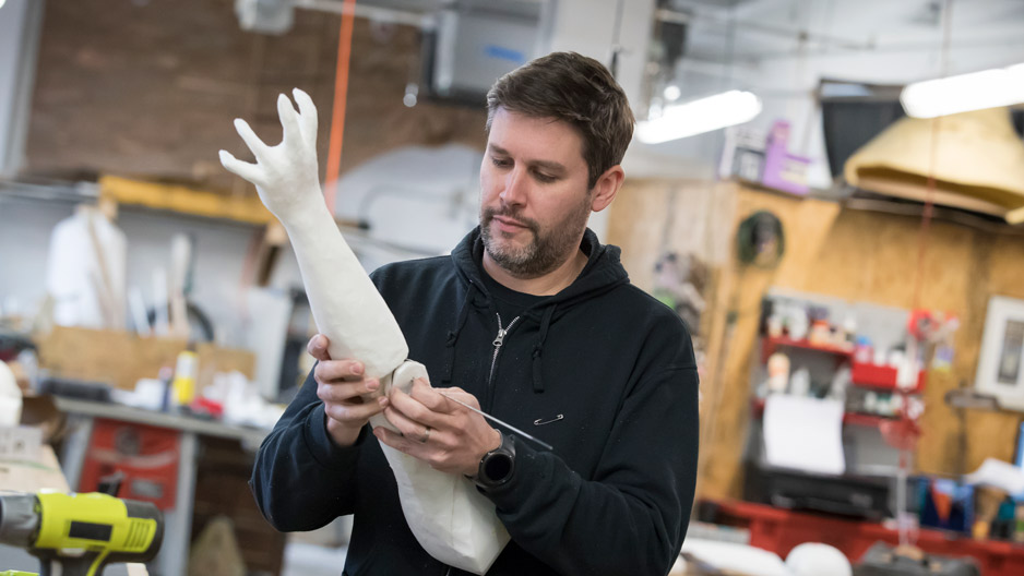 Michael Latini examining a puppet he's making for a Broadway show