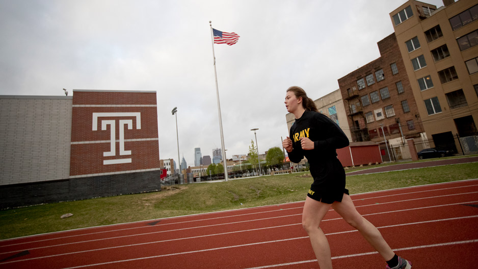 a female ROTC student runs by a building with the Temple 'T'