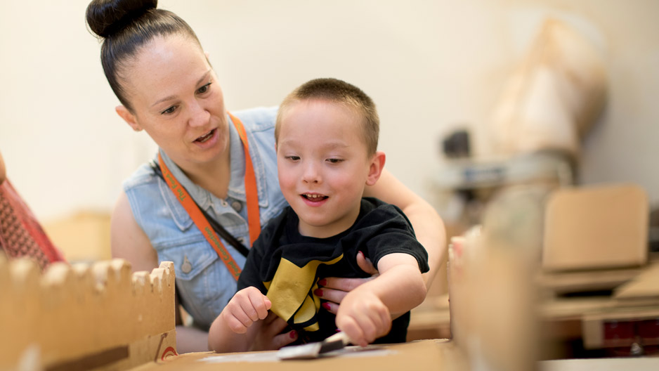 Mark Ovington, 5, painting a cardboard adaptation with help from mom