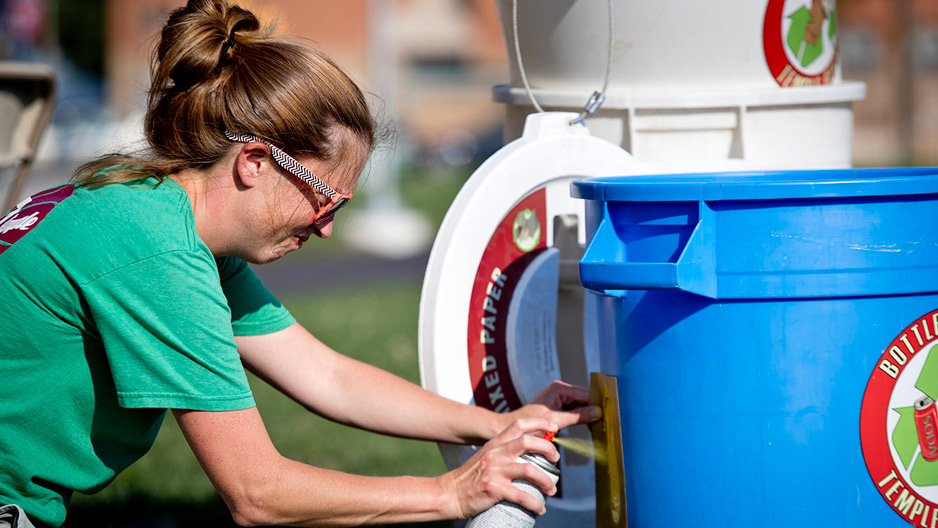 Kathleen Grady spray painting an address onto a recycling bin