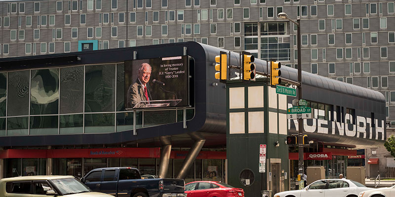 A screen memorializing Gerry Lenfest at a busy intersection in North Philadelphia