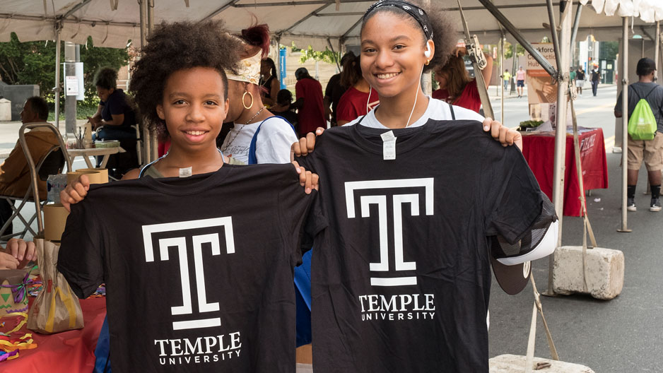 Girls hold up Temple 'T' T-shirts
