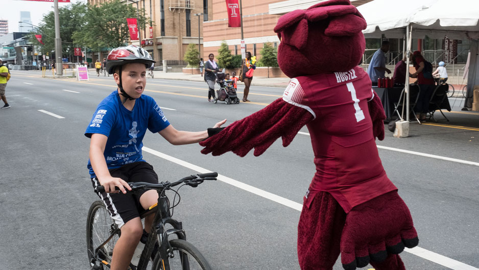 Boy on bike high fives Hooter