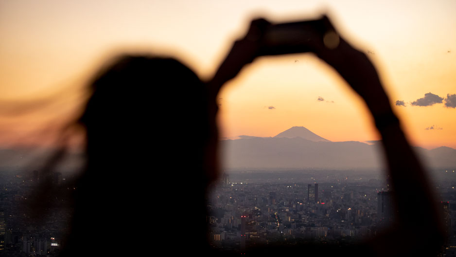 person holding phone up to take a photo of Mt. Fuji