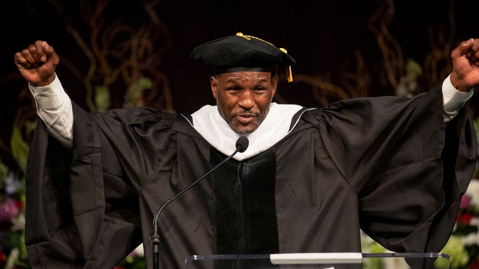 Bernard Hopkins raising his fists while giving a Commencement address