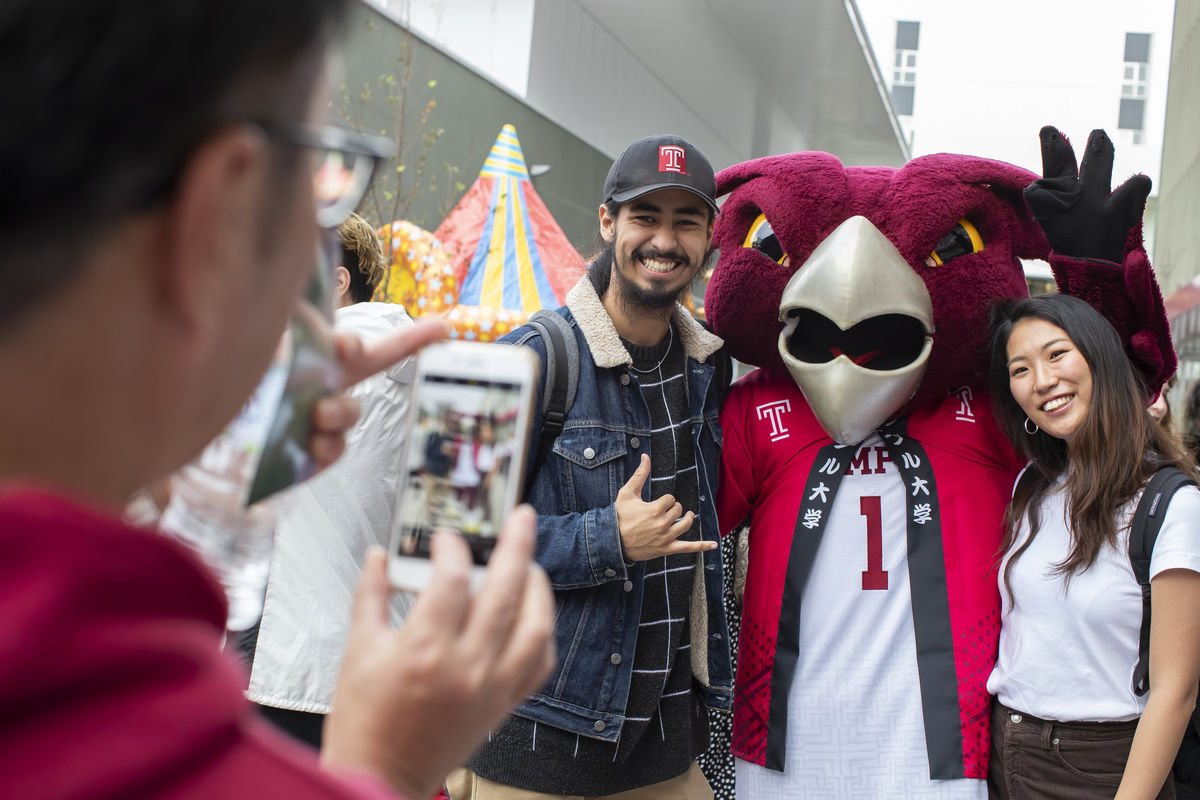 Students take pictures with Temple University's mascot, Hooter the Owl.