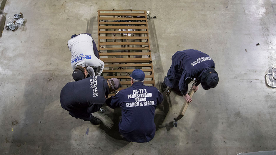 Task force members moving a hospital bed frame