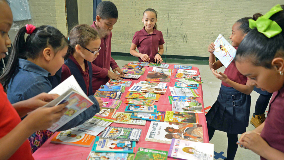 children standing at a table full of books.