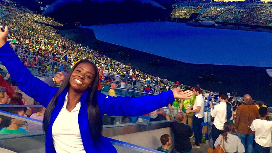 A woman in white shirt and blue jacket smiling at the Summer Olympic Games.