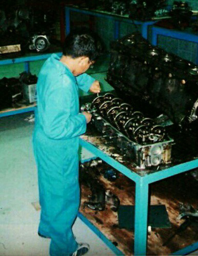 young student working on car engine
