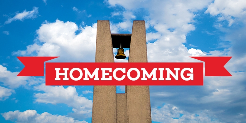 "A banner reading ""Homecoming"" in front of the Bell Tower."
