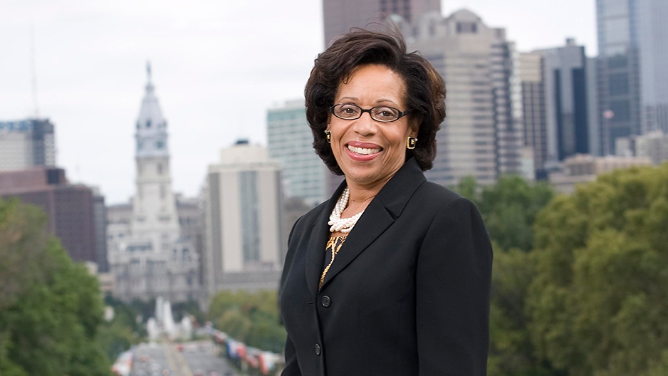 A woman in glasses and a black jacket standing before Philadelphia's skyline.