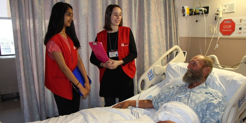 Two patient ambassador students talking with a patient