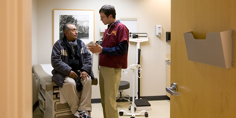 A doctor interacting with a patient inside an exam room.