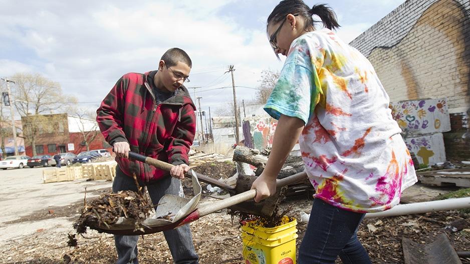 Two volunteers shoveling dirt into buckets.