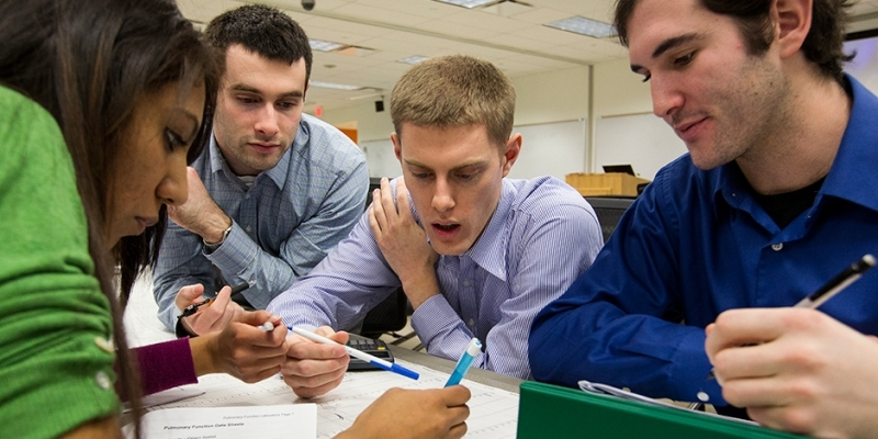 Four students around a table working on an assignment.
