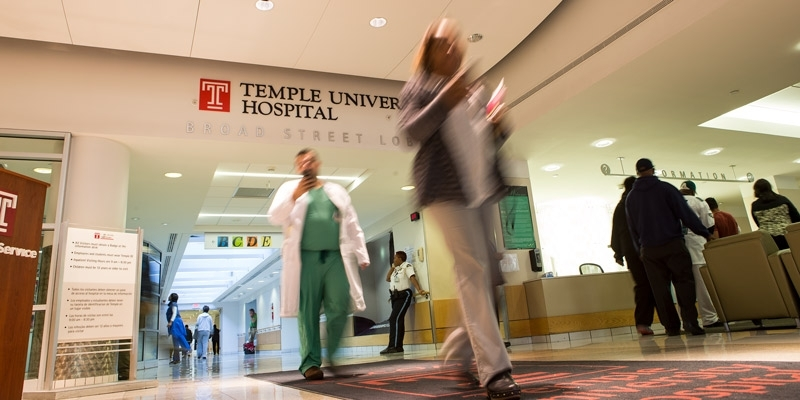 People walking through the entrance to Temple University Hospital.