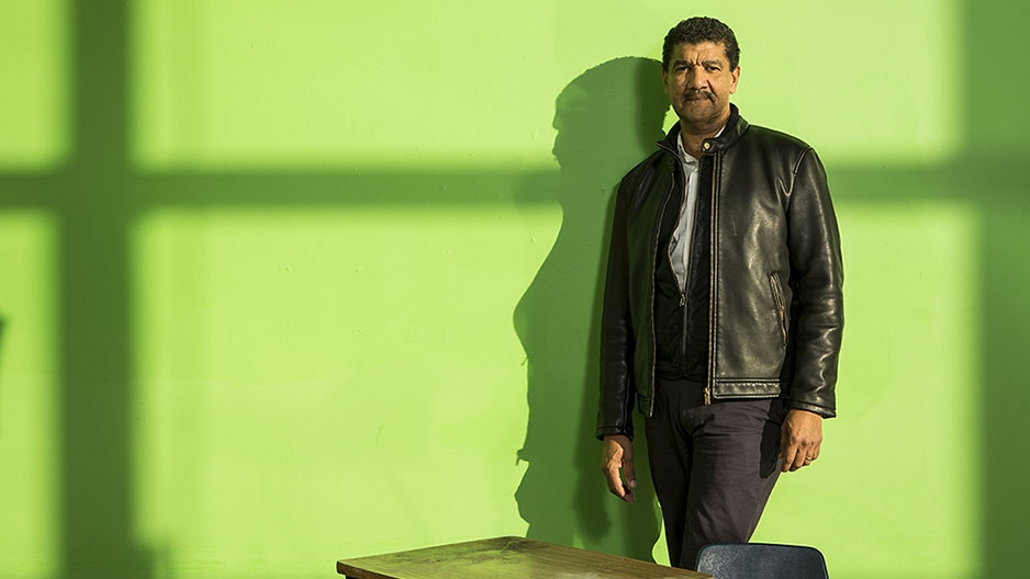 Pepón Osorio standing in front of a green wall.