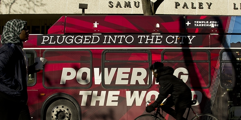 A Temple bus wrap that reads 'plugged into the city, powering the world' outside of Paley library.