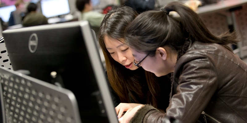 Two women sitting in front of a computer