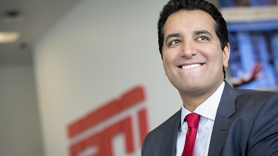 Kevin Negandhi smiling with an ESPN logo in the background.