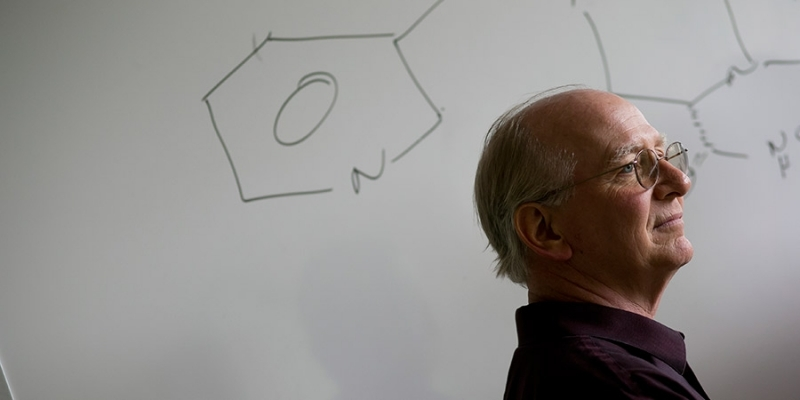 Jim Guare standing in front of a drawing of a chemical compound.