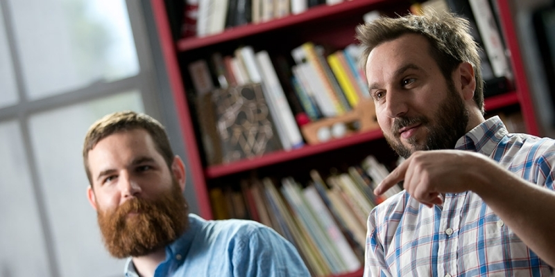 Two male Temple alumni working in their graphic design studio.