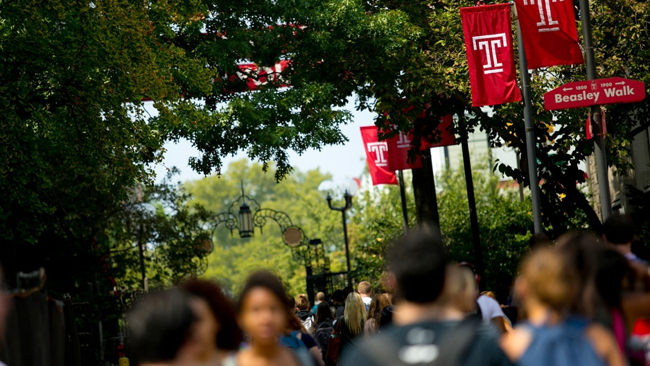 Students walking on campus under Temple 'T' flags.