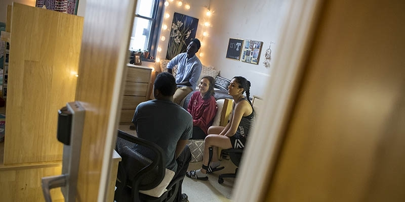 Several students sitting together in a residence hall room.