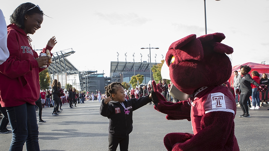 A little girl giving Hooter a high five at a tailgate outside Lincoln Financial Field.