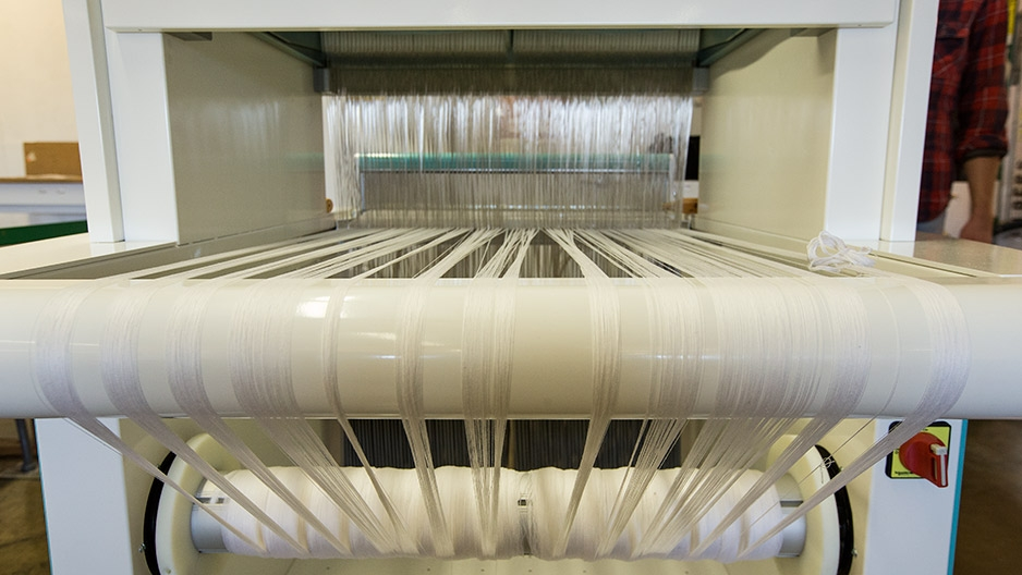 White fabric spinning on a loom.
