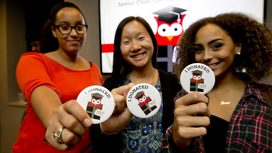 "Three students each holding a sticker that says ""I donated."""