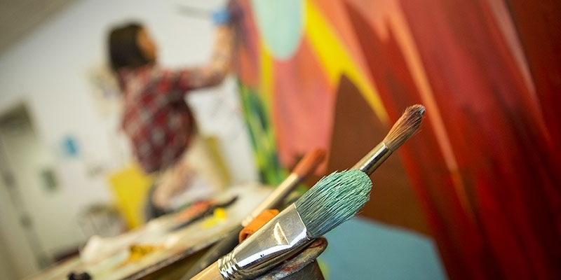 Paintbrushes and a woman painting in the background.
