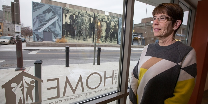 Sister Mary Scullion standing in front of a window, looking out on a mural.