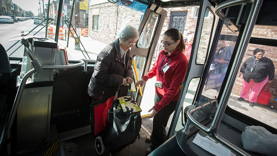 A young woman helping an older woman carrying a cart safely board a bus.
