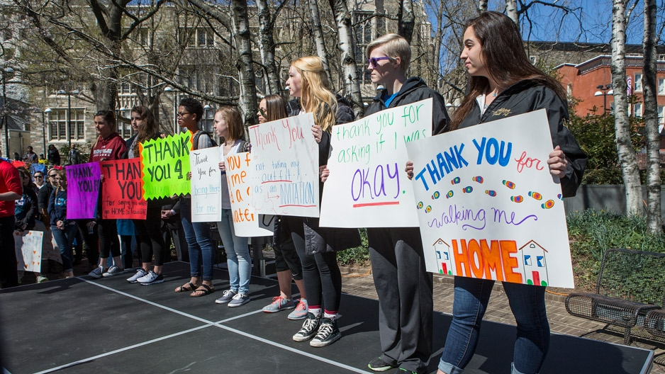 Students holding signs during a walk to raise awareness around sexual assault.