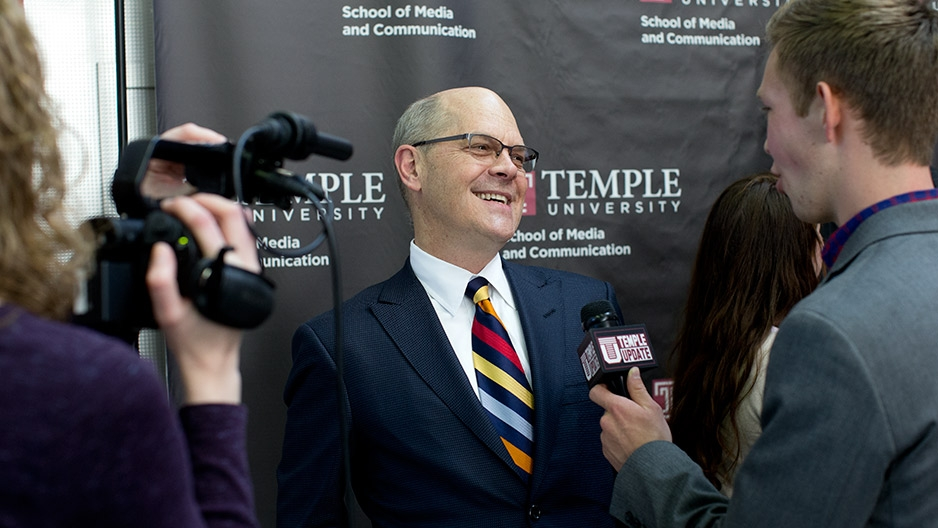 Steve Charles smiling while being interviewed on camera by Temple Update.