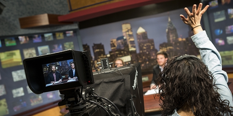 Students in a TV studio preparing to shoot a news segment.
