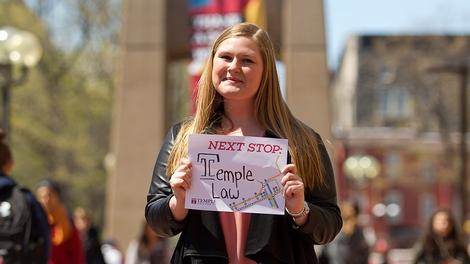 A woman in a black jacket holding a sign in front of Temple's bell tower.