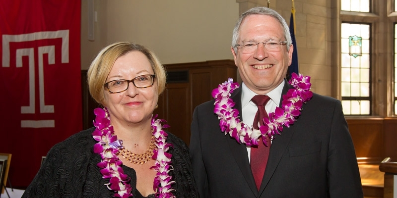 Elizabeth Bolman and President Neil D. Theobald wear flower leis and smile.
