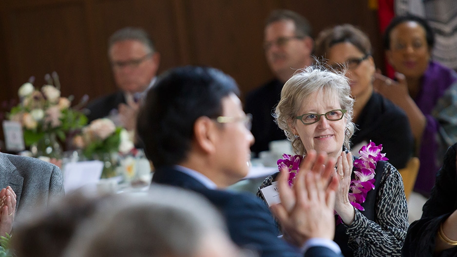 A female faculty member applauding during Temple's Faculty Awards Luncheon.