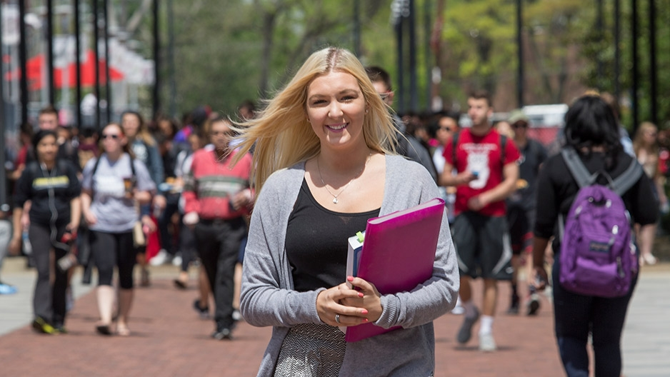 A blond woman holding books on Liacouras Walk.