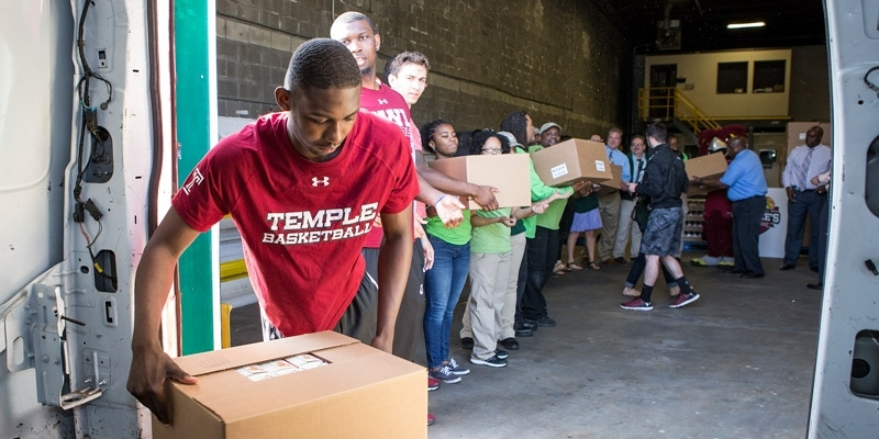Temple men's basketball players unloading a van at a food bank.